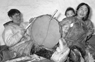 Black-and-white photograph of an Inuit man playing a drum while a woman listens with her baby