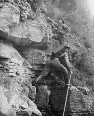 Photograph of two men climbing up the side of a mountain, 1887