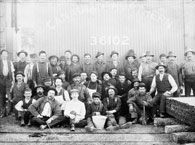 Photograph of a group of railway workers. The waterboy is sitting in the front row