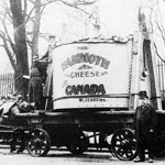 Photograph of horses pulling a wagon carrying the big cheese