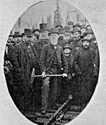 Photograph of Donald Smith holding a hammer, at a ceremony to drive in the last spike of the Canadian Pacific Railway. Edward Mallandaine can be seen in the background