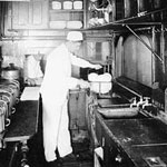Photograph of a cook working in the kitchen of a Canadian Northern Railway kitchen car, 1915