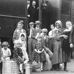 Photograph of Hungarian immigrants standing on the platform in front of a train, 1920