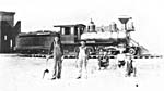 Photograph of railway workers standing in front of a train, including the fireman with his coal shovel