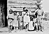 Photograph of a group of Black children leaning against a log home, Athabasca Landing, Alberta