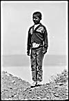 Photograph of a young boy from Africville, standing on a hill, 1965
