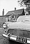Photograph of a man from Africville leaning on a car, 1965