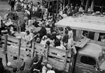Photograph of Japanese Canadians being loaded onto trucks en route to internment camps in the interior of British Columbia, 1942