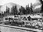 Photograph of a Chinese railway workers' log camp beside railroad