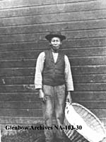 Photograph of an Innisfail Laundry employee carrying a wicker laundry basket, Innisfail, Alberta