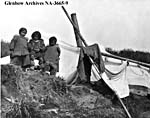 Photograph of three Inuit children in front of a tent