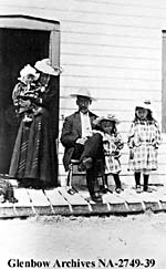Photograph of a Métis family on the porch of their home