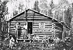 Photographs of settlers in frot of a log house, Val-d'Or, Québec