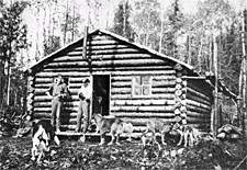Photographs of settlers in frot of a log house, Val-d'Or, Québec, 1932