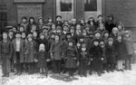 Photograph of Finnish immigrant children posing for a photograph in front of a building in winter, Toronto, Ontario, 1935