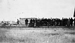 Photograph of a large group of Jewish immigrants waiting alongside the railwoad, Oungre, Saskatchewan, 1928