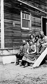 Photograph of a family of immigrants sitting on steps of a house, Edenbridge, Saskatchewan, 1939