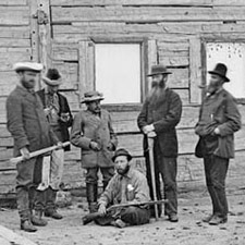 Photograph of George M. Dawson and his survey party in front of a wooden building at Fort McLeod, British Columbia, 1879