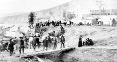 Photograph of Dawson City, Yukon, showing people crossing a footbridge and walking along a wooden street lined with wooden houses, 1898