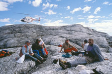Photograph of a geological survey party eating lunch on a Hurwitz quartzite outcrop with their helicopter in the background, 1997