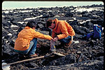 Photograph of two geologists collecting material in a boulder field on Melville Peninsula, Nunavut