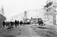 Photograph of Dawson City, Yukon, showing people walking along a dirt street with buildings, some under construction, on either side, 1898
