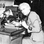Photograph of Alice Wilson in her office looking through a microscope