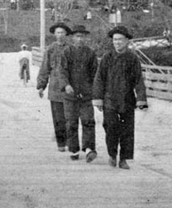 Photograph of five men walking on quay toward camera, with Union Jack flag, tall trees and small wooden building in background