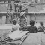 Photograph of four adults and three children on deck of ship, with sailing mast in background