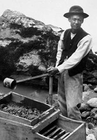 Photograph of man standing at edge of river with gold-washing equipment