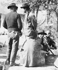 Photograph of group of men at campsite with laundry hanging to dry