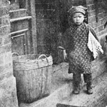 Photograph of small child standing on front step of brick storefront among baskets