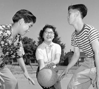 Photograph of three youth playing basketball. Two boys poised for jump-off, as girl holds ball between them