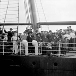 Black and white photograph of a large group of people standing on the deck of a ship