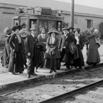Black and white photograph of a group of immigrants standing near railroad tracks
