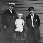 Black and white photograph of two men in uniforms and a small child
