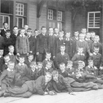 Black and white photograph of a large group of boys posing outside a building