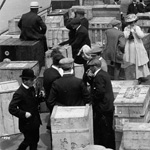 Black and white photograph of people standing amongst baggage on the deck of a ship
