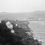 Black and white photograph of a few white cabins and houses on a rocky shoreline as seen from a hill