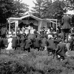 Black and white photograph of a crowd of well-dressed people kneeling in grass in front of a stage