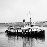 Black and white photograph of a small steam ship with buildings and a light house in the distance