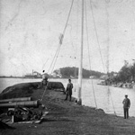Black and white photograph of two men standing near several cannons on a bay