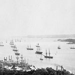 Black and white photograph of sailing ships and a harbour seen from high above