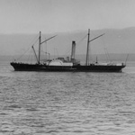 Black and white photograph of a small steamship with land in the distance