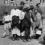 Black and white photograph of a group of people standing with their luggage outside a building