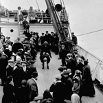 Black and white photograph of a group of people on the deck of a ship watching two boys playing leap frog