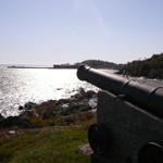 Photograph looking down the barrel of a cannon towards the shoreline of Grosse��le with buildings in the distance