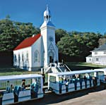 Colour photograph of a white church, tourist trolley and trees in the background