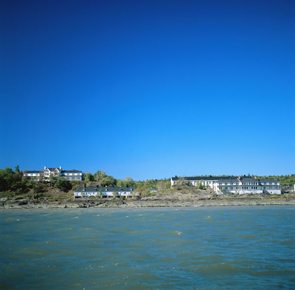 Photograph of four buildings on a shoreline as seen from the water