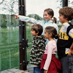 Photograph of a group of four children looking at engraved names on a large glass plaque